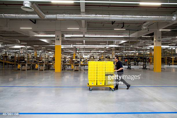 An employee pushes yellow product crates on a trolley across the work floor at the new Amazon Inc fulfilment center on its official day of opening in...
