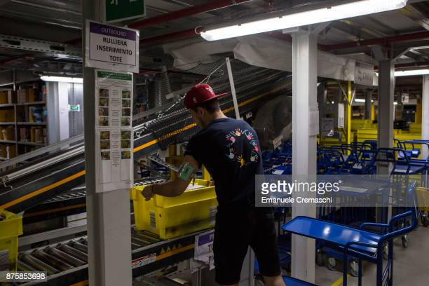 An employee puts a box filled with merchandise on a conveyor belt at the Amazoncom MPX5 fulfillment center on November 17 2017 in Castel San Giovanni...