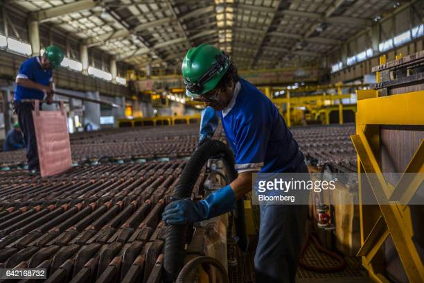 An employee puts chemicals in a large acidfilled tank during the electrolytic refining process of copper anodes at the Southern Copper Corp refinery...