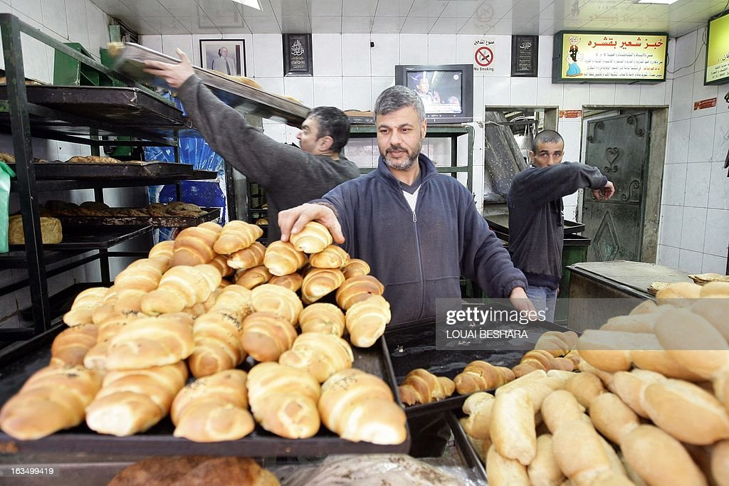 An employee puts croissants on a display shelve at a bakery on March 7, 2013 in the Syrian capital Damascus. Two years into the civil war, Syrians spend long nights queuing in their cars for fuel, while others pay bribes to secure gas for the home, and families share information on the location of the nearest open bakery.