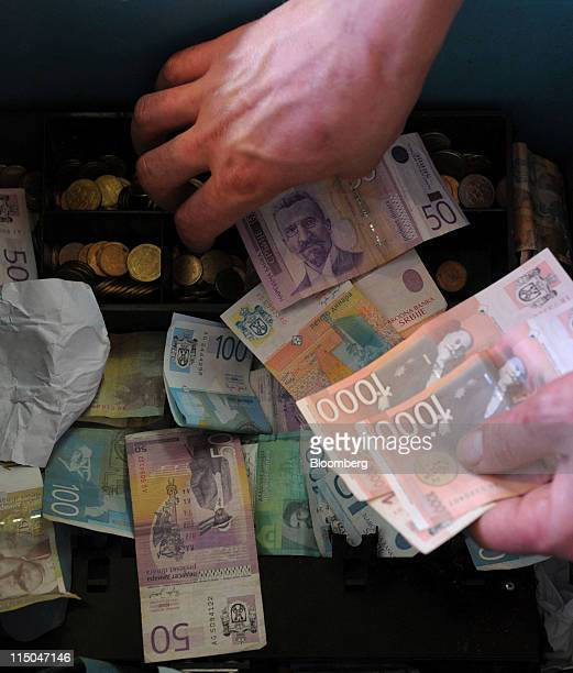 An employee puts dinar notes in the till at a market in Belgrade Serbia on Wednesday June 1 2011 Serbia's economy is emerging from a recession with...