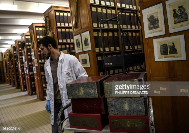 An employee puts on a cart binders containing herbarium paper sheets to have the sheets digitalizated on March 12 2018 at the Claude Bernard LyonI...