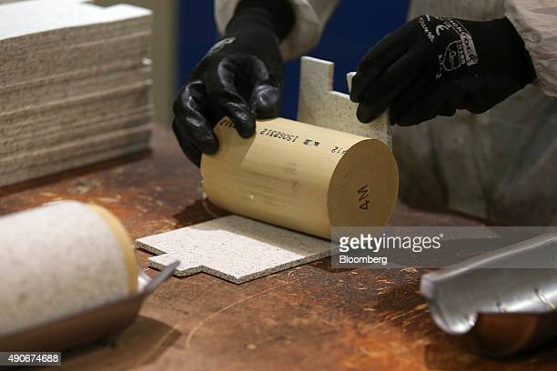 An employee puts together an automobile catalytic converter emission control device using a 'brick' or monolith that contains platinum at BM...
