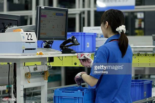 An employee puts together robotsorted and humansorted products at a Toho Pharmaceutical Co distribution center in Kuki Saitama Prefecture Japan on...