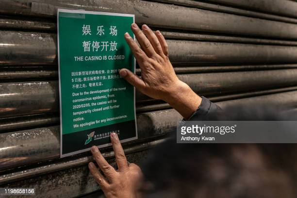 An employee puts up a closing notice on the gate of the main entrance of Casino Lisboa after its closing on February 5, 2020 in Macau, China. Macau...