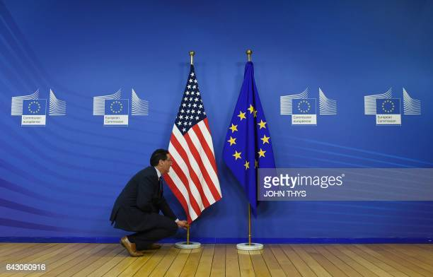 An employee puts up the US flag next to the flag of the EU prior to a meeting between the EU Commission President and the US VicePresident at the EU...