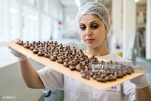 An employee quality checks a tray of chocolates inside the Lindt Spruengli AG factory in Kilchberg Switzerland on Tuesday July 29 2014 Lindt the...