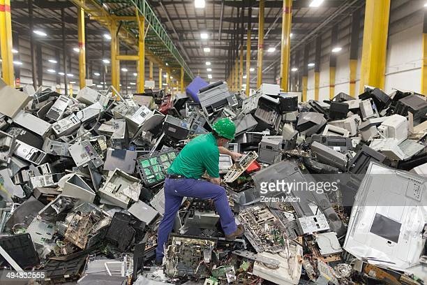 An employee reaches examines electronic waste awaiting to be dismantled as recyclable waste at the Electronic Recyclers International plant in...