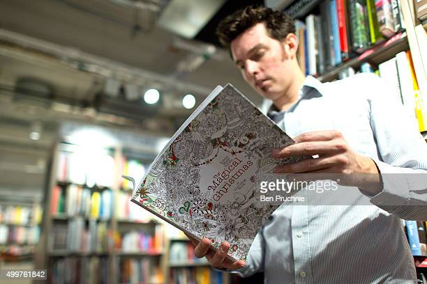 An employee reads a copy of 'The Magical Christmas' colouring book in Foyles bookshop on December 3 2015 in London United Kingdom Foyles flagship...