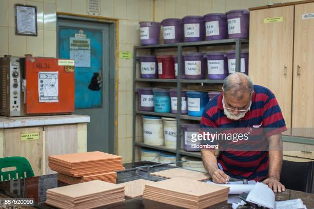 An employee records data after examining sample tiles in the laboratory at the Shabbir Tiles Ceramics Ltd production facility in Karachi Pakistan on...