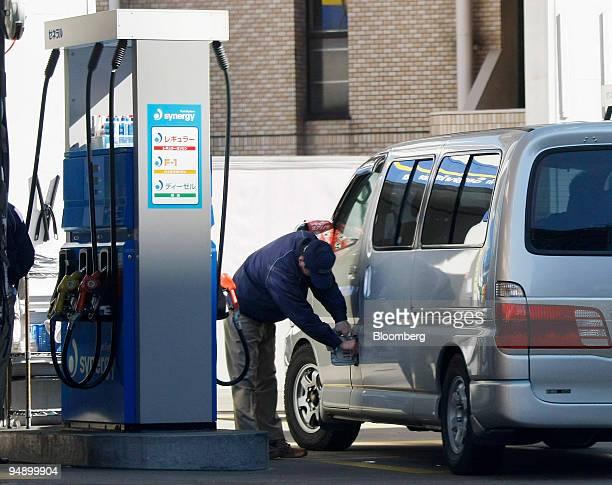 An employee refuels a vehicle at a TonenGeneral gas station in Tokyo Japan on Thursday Feb 14 2008 TonenGeneral Sekiyu KK a unit of Exxon Mobil Corp...