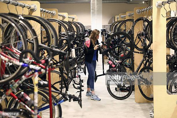 An employee removes a bicycle from its hanger at the Rapha Racing Ltd headquarters office in London UK on Thursday Nov 10 2016 To keep ahead of the...