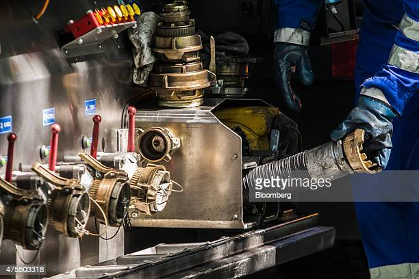 An employee removes a fuel hose from a petrol tanker as he prepares to refuel petrol pumps at a gas station operated by MOL Hungarian Oil Gas Plc in...