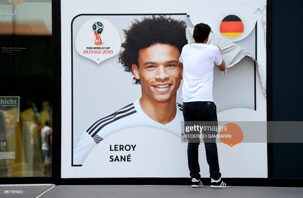 An employee removes a poster bearing a portrait of the German national player Leroy Sane from the facade of the Football Museum of the German Football Federation (DFB) on June 4, 2018 in Dortmund, western Germany, after the national coach Joachim Loew announced the final squad of the German national soccer team for the upcoming World Cup 2018 in Russia. - In a surprise omission, coach Joachim Loew left Manchester City striker Leroy Sane out of his 23-player list despite a strong season with the Premier League champions. (Photo by Federico Gambarini / dpa / AFP) / Germany OUT