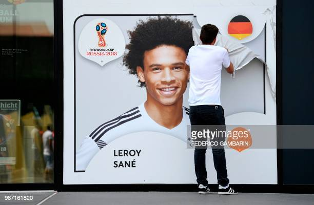 An employee removes a poster bearing a portrait of the German national player Leroy Sane from the facade of the Football Museum of the German...