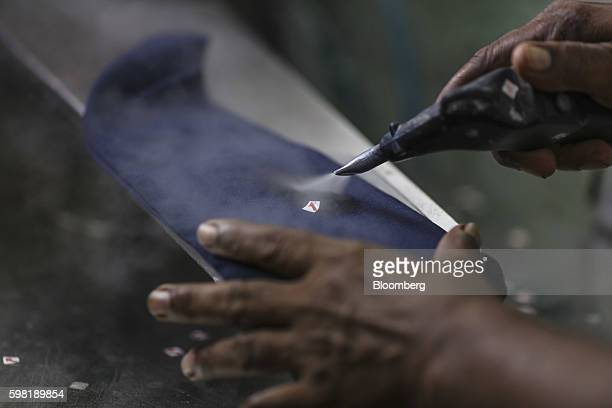 An employee removes a sticker from a garment at the CBC Fashions Pvt factory in Tiruppur Tamil Nadu India on Thursday Aug 4 2016 India's $17 billion...
