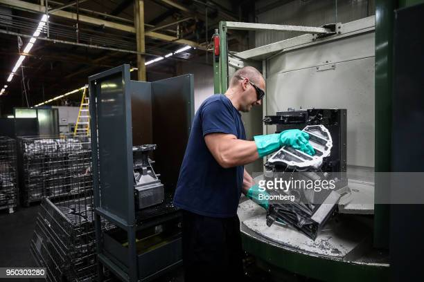 An employee removes excess water from a cutting machine at Liberty Aluminium Technologies in Coventry UK on Monday April 23 2018 Aluminum markets are...