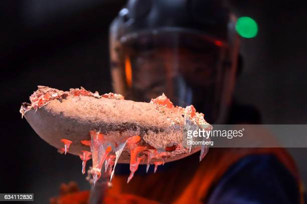 An employee removes impurities from the surface of a bucket of liquid aluminum at the Lochaber aluminum smelter operated by Liberty House Group in...