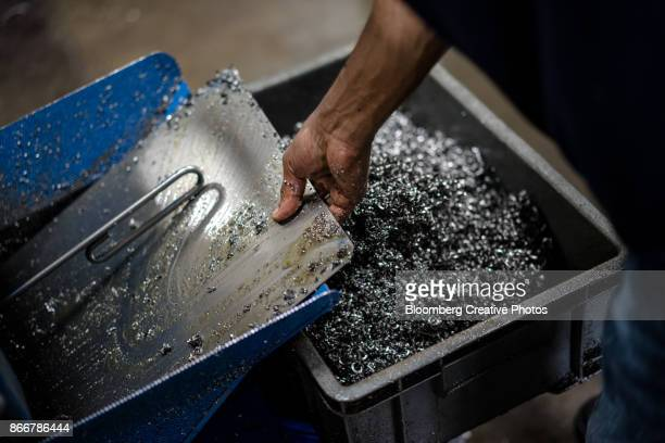 an employee removes metal shavings from a tray at a manufacturing facility - shah alam stock photos and pictures