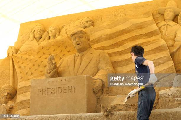 An employee removes waste sand front of the sand sculpture of US President Donald Trump during the 10th Annual Sand Sculpture Exhibition of 'Travel...