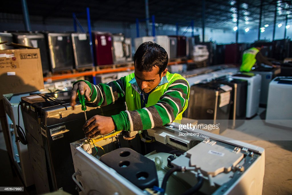 An employee repairs a washing machine in the home appliances section at the refurbishment facility of GreenDust, a unit of Reverse Logistics Co., in New Delhi, India, on Friday, Jan. 16, 2015. Reverse Logistics, an Indian retailer of refurbished goods, is a factory outlet store in India selling goods through its GreenDust, a unit of Reverse Logistics Co., brand franchise stores and website. Photographer: Prashanth Vishwanathan/Bloomberg via Getty Images