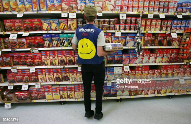 An employee restocks a shelf in the grocery section of a WalMart Supercenter May 11 2005 in Troy Ohio WalMart America's largest retailer and the...