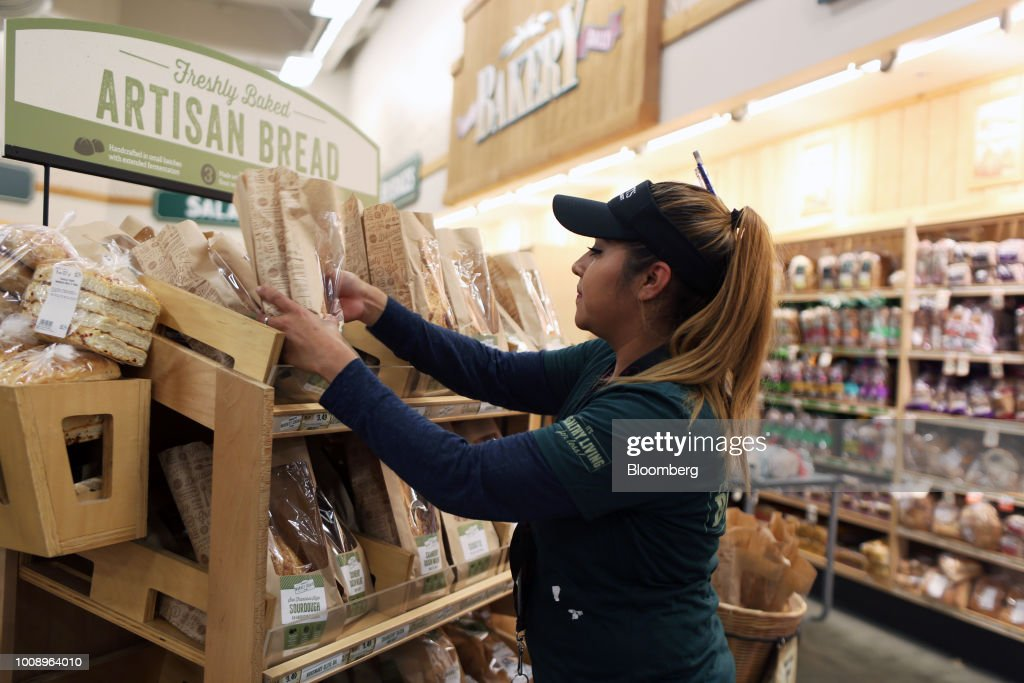 An employee restocks a shelf with loaves of bread at a