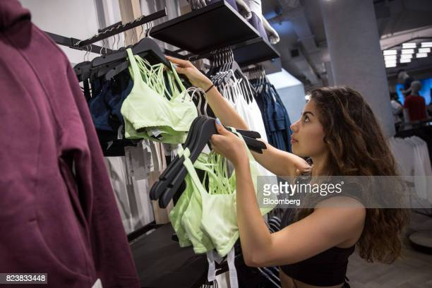 An employee restocks clothes on display at the Lululemon Athletica Inc. Sports apparel store on Regent Street in London, U.K., on Thursday, July 27,...