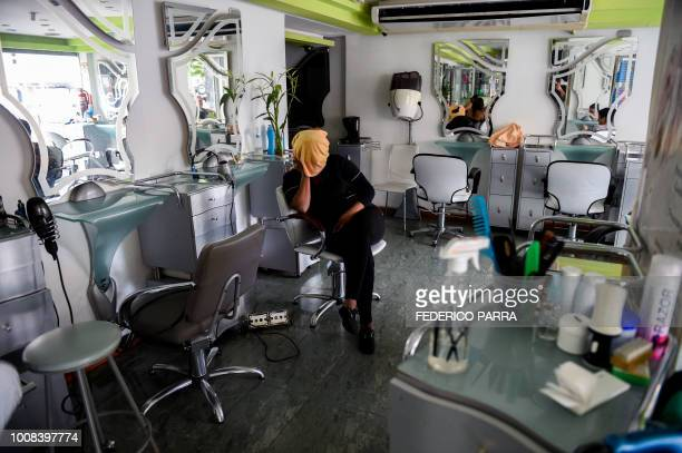 An employee rests inside a hairdressing salon during a partial power cut in Caracas on July 31 2018 A power failure cut electricity to 80 percent of...