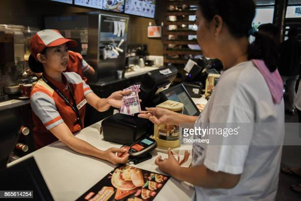 An employee returns change and a card to a customer at the counter of a Jollibee Foods Corp restaurant in Bonifacio Global City triangle in the...