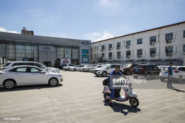 An employee rides a scooter past Ford Motor Co vehicles at a Ford dealership in Shanghai China on Thursday July 19 2018 The fledgling USChina trade...