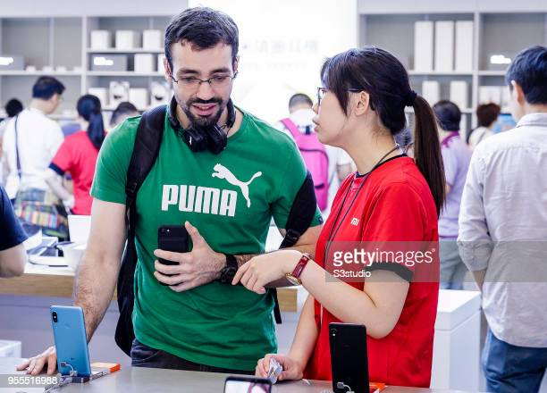 An employee right assists a customer as he looks at a Xiaomi Corp Mi MIX 2S smartphone inside of the Xiaomi Corp store on Nathan Road in Hong Kong on...