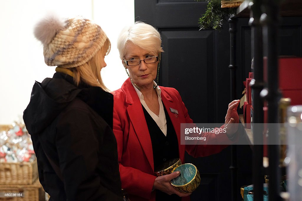 An employee, right, assists a customer inside a pop-up store, operated by Fortnum & Mason Plc, during a seasonal Christmas event at Somerset House in London, U.K., on Tuesday, Dec. 9, 2014. The British will be the biggest spenders in Europe on Christmas gifts this year, according to a study commissioned by Dutch bank ING Groep NV. Photographer: Simon Dawson/Bloomberg via Getty Images