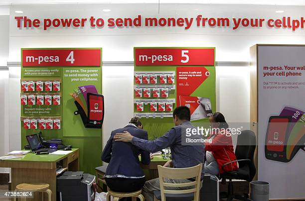 An employee right assists customers with enquiries about Mpesa 4 and Mpesa 5 mobile payment systems at a store inside the headquarters of Vodacom...