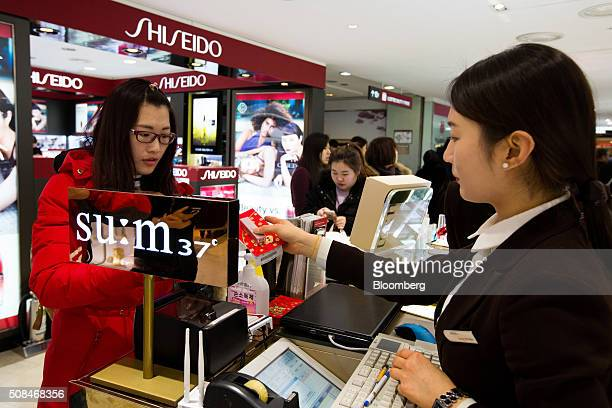 An employee right hands a product to a customer at a cosmetics booth in a Hotel Lotte Co Duty Free store in Seoul South Korea on Thursday Feb 4 2016...