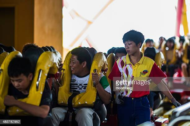 An employee right inspects the safety restraints as visitors prepare to ride the Hair Raiser roller coaster at the Ocean Park operated by Ocean Park...