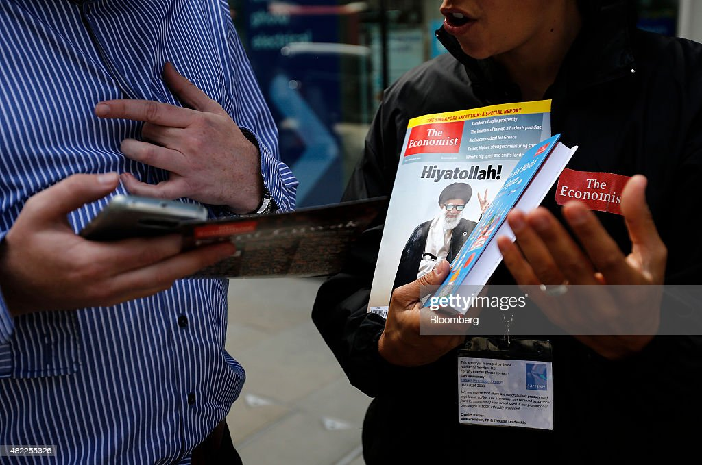 An employee, right, talks with a potential customer while holding a copy of The Economist magazine in London, U.K., on Wednesday, July 29, 2015. Pearson Plc moved closer to an exit from business publishing as it announced plans to dispose of its stake in the 172-year-old Economist magazine, just days after the sale of the Financial Times newspaper. Photographer: Simon Dawson/Bloomberg via Getty Images
