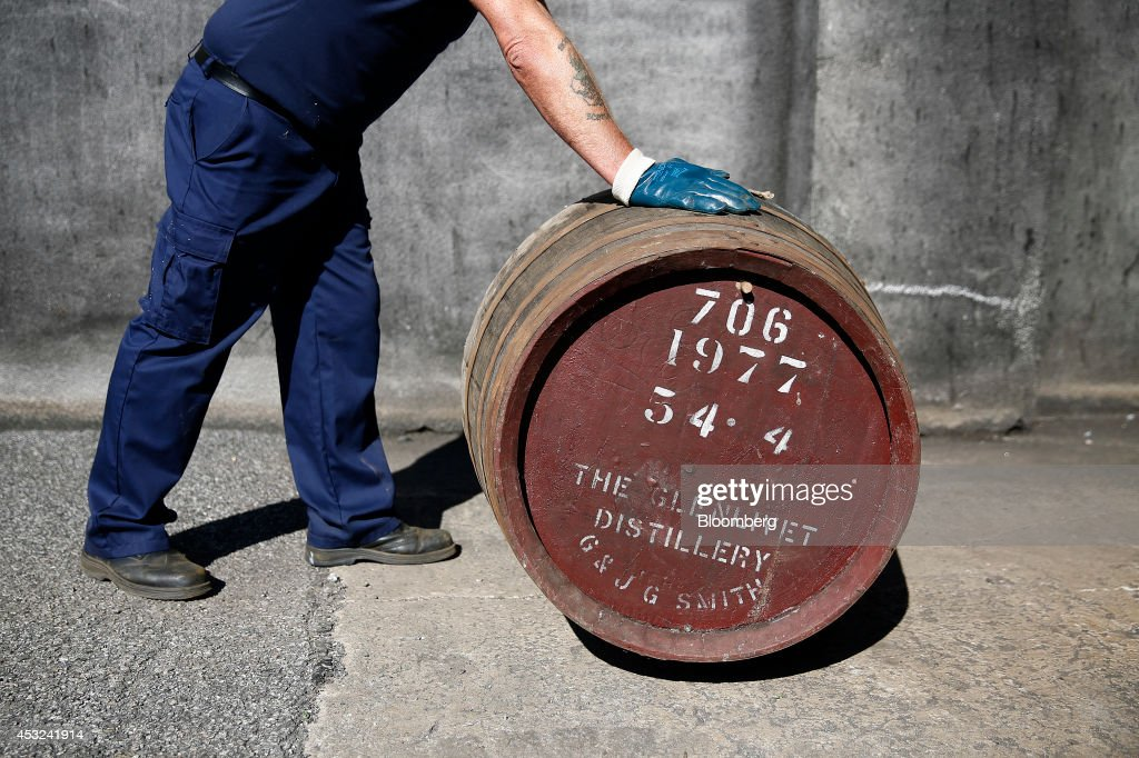 An employee rolls a cask of The Glenlivet single malt whisky, produced by Pernod Ricard SA, into a storage warehouse at the company's bottling plant in Ballindalloch, U.K., on Tuesday, Aug. 5, 2014. Scottish nationalist leader Alex Salmond and former Chancellor of the Exchequer Alistair Darling, who leads the 'No' campaign, clashed over the risks and merits of independence six weeks before the Sept. 18 referendum that could bring an end to the U.K. Photographer: Simon Dawson/Bloomberg via Getty Images