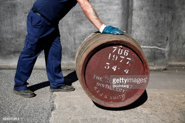 An employee rolls a cask of The Glenlivet single malt whisky produced by Pernod Ricard SA into a storage warehouse at the company's bottling plant in...
