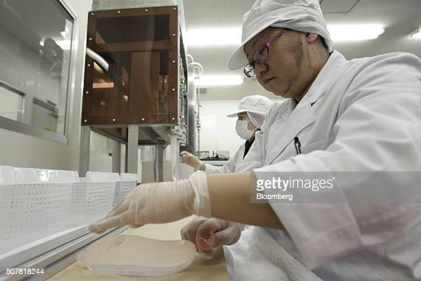 An employee rolls a latex condom during a water leaking test at a Sagami Rubber Industries Co factory in Atsugi Kanagawa Prefecture Japan on Thursday...