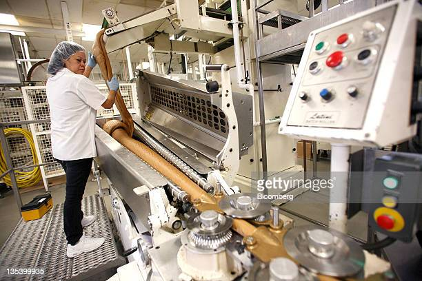 An employee rolls butterscotch mix into heated batch rollers to make lollipops at the See's Candies Inc lollipop factory in Burlingame California US...