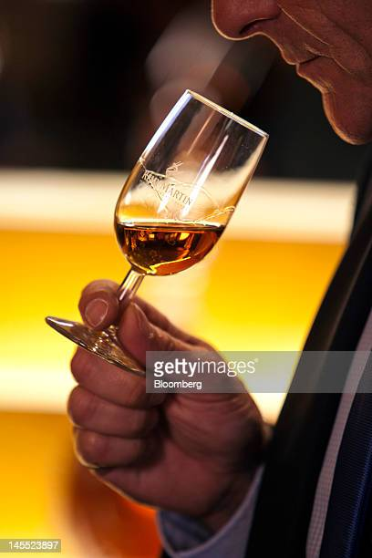 An employee samples a glass of cognac poured from a bottle of Remy Martin VSOP Mature Cask Finish Cognac at the Remy Cointreau SA headquarters in...