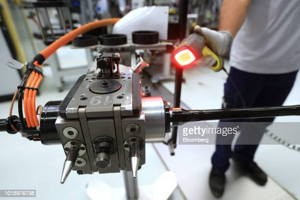 An employee scans a barcode on the luxury automobile electromechanical axle roll control device assembly line inside the Schaeffler AG factory in...