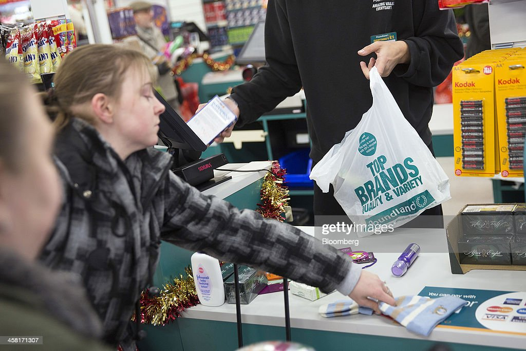 An employee scans a customer's goods at a check-out desk inside a Poundland discount store, operated by Poundland Holdings Ltd., in Birmingham, U.K., on Friday, Dec. 20, 2013. U.K. discount retailer Poundland has hired Rothschild to manage its IPO, according to the Sunday Times newspaper. Photographer: Simon Dawson/Bloomberg via Getty Images