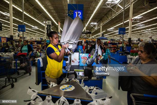 An employee scans a customer's purchases at a Walmart Inc store in Secaucus New Jersey US on Wednesday May 16 2018 Walmart is scheduled to release...