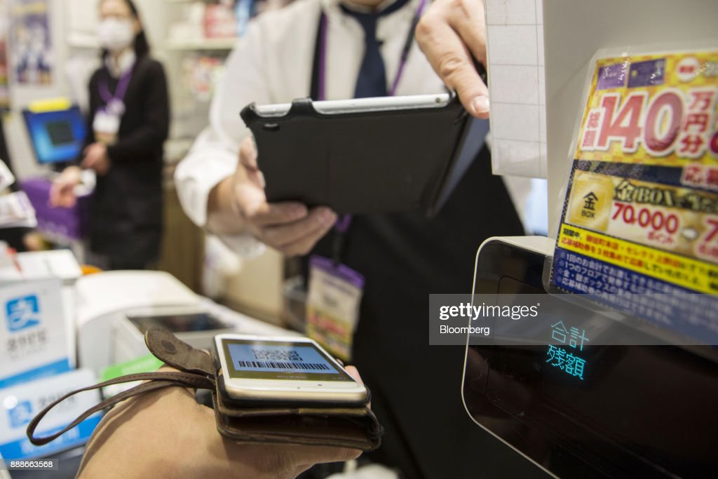 An employee scans a quick response (QR) code displayed on the Ant Financial Services Group's Alipay app, an affiliate of Alibaba Group Holding Ltd., at a Takeya Co. Ueno Select shop in Tokyo, Japan, on Saturday, Dec. 9, 2017. Ant Financial and its strategic partners outside China should be able to nearly double users of their payments systems in coming years, Ant's overseas operations president Douglas Feagin said on Nov. 14. Photographer: Shiho Fukada/Bloomberg via Getty Images