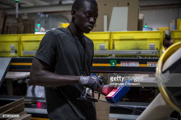 An employee scans an item before packing a box of merchandise at the Amazoncom MPX5 fulfillment center on November 17 2017 in Castel San Giovanni...