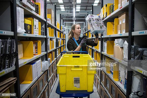 An employee scans merchandise as she collects items for a customer's delivery order from an Amazon.com Inc. Fulfillment center in Peterborough, U.K.,...