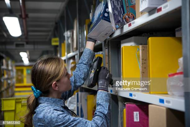 An employee scans merchandise as she collects items for a customer's delivery order from at the Amazoncom MPX5 fulfillment center on November 17 2017...