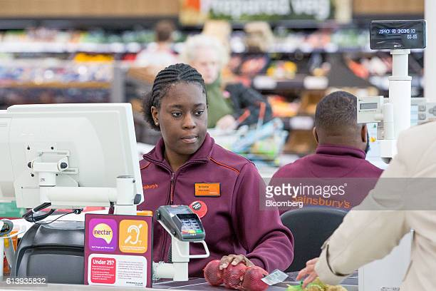 An employee scans onions at a checkout in the J Sainsbury Plc flagship store in London UK on Tuesday Oct 11 2016 J Sainsbury Plc agreed to buy Home...